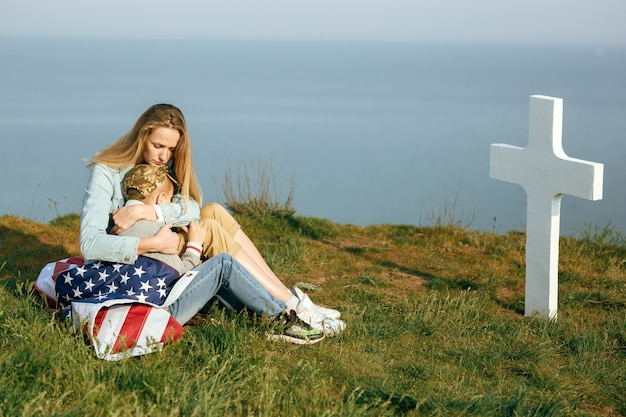 Maman Et Son Fils Sont Assis Sur La Tombe D'un Soldat. Maman A Amené Son Fils Sur La Tombe De Son Père Le 27 Mai Photo Premium