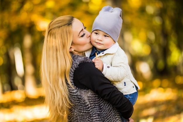 Maman Et Son Fils Sont Dans Le Parc D'automne, Le Fils Adore Regarder Sa Mère, La Femme Tient Ses Mains Photo gratuit
