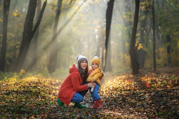 Maman Souriante Et Sa Fille En Promenade. Journée Ensoleillée Au Parc D'automne Photo Premium