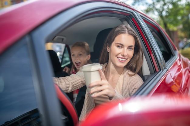 Maman Souriante Tenant Une Tasse De Café, Conduisant Avec Sa Fille étonnée Photo Premium