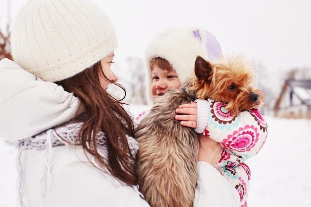 Maman tient sa fille et doggy Photo gratuit