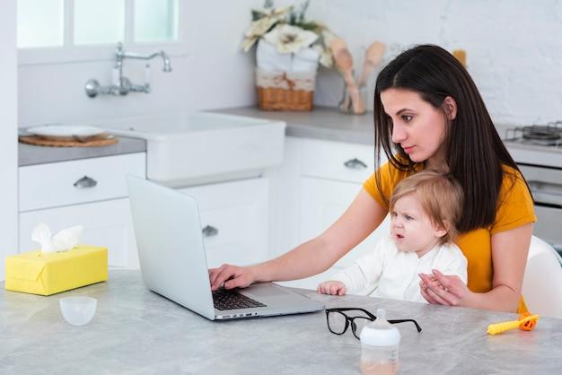 Maman travaille sur un ordinateur portable en tenant bébé Photo gratuit