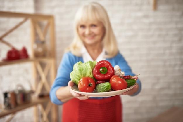 Mamie souriante détient les légumes frais cultivés à la maison. Photo Premium