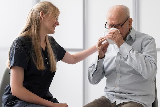 Man Boire De L'eau Avec Une Infirmière Le Consolant Photo Premium