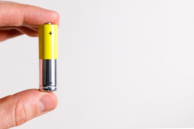 Man Hand Holding Alcaline Battery Aa Size, Close Up, Isolated On White Background With Copy Space. Photo Premium