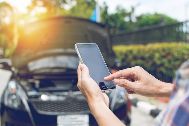 Man phoning pour de l'aide avec une voiture en panne Photo Premium