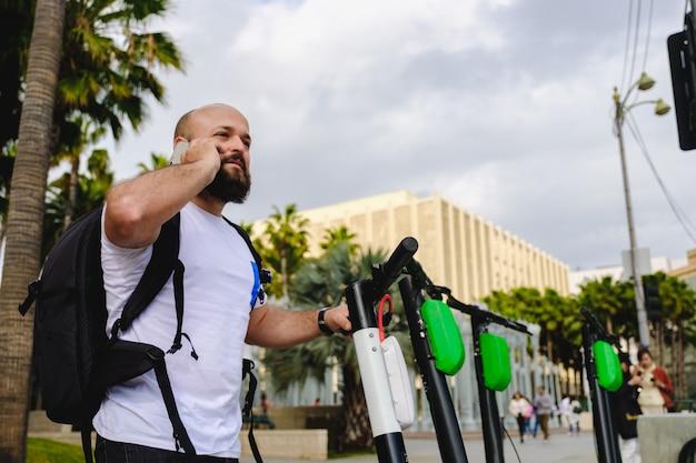 Man Scanning Qr Code Avec Son Téléphone Pour La Location De Scooter électrique Photo Premium