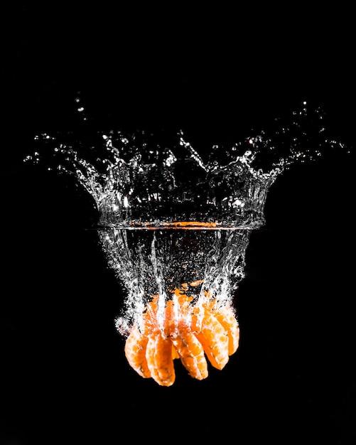 Mandarine plongeant dans l'eau Photo gratuit