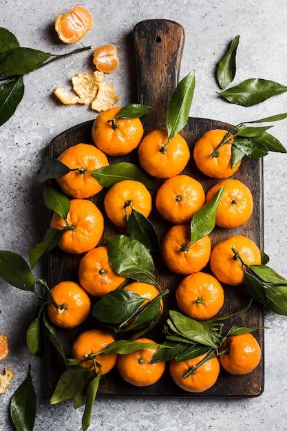 Mandarines avec des feuilles vertes sur une planche de bois sur la lumière Photo gratuit