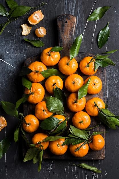 Mandarines avec des feuilles vertes sur une planche en bois sombre Photo gratuit