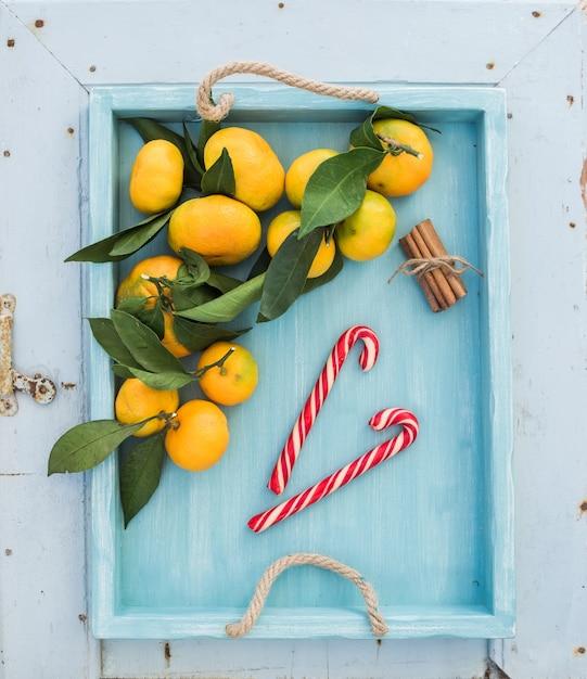 Mandarines fraîches avec des feuilles, des bâtons de cannelle et des cannes de bonbon de noël dans un plateau turquoise sur la toile de fond en bois rustique bleue, vue de dessus. Photo Premium