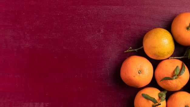 Mandarines pour le nouvel an chinois avec fond rouge Photo gratuit