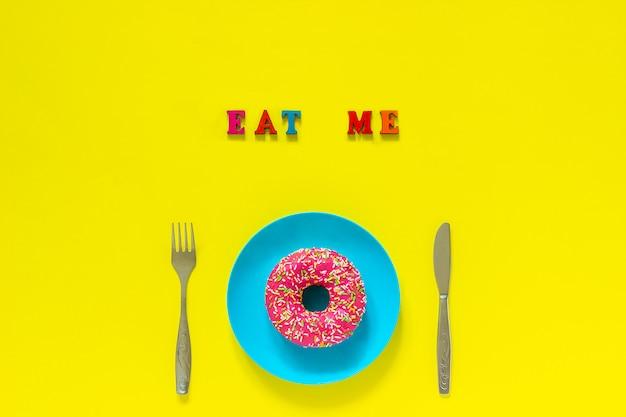 Mange-moi un beignet rose sur une assiette bleue et une fourchette à couteau sur fond jaune. Photo Premium