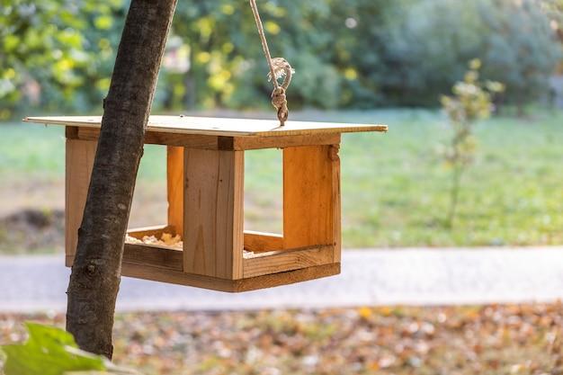 Mangeoire à Oiseaux En Bois Maison Sur Un Arbre Dans Le Parc Automne. Photo Premium