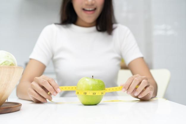 Manger sainement et concept de régime. fille utiliser du ruban à mesurer mesure pomme verte sur la table. Photo Premium