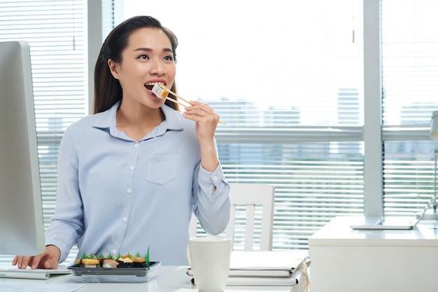 Manger des sushis au travail Photo gratuit