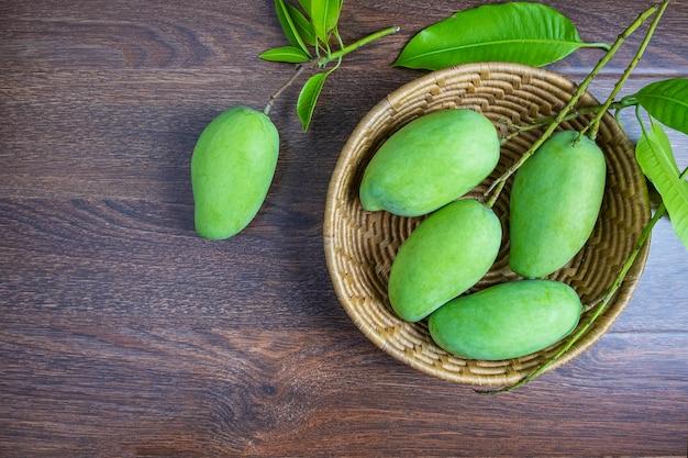 Mangue verte fraîche dans un panier en bois Photo Premium