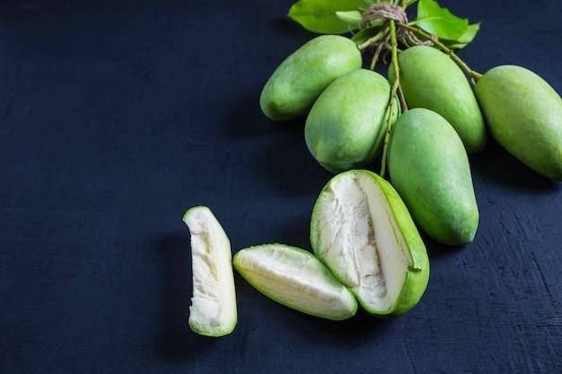Mangue verte fraîche sur une table en bois Photo Premium