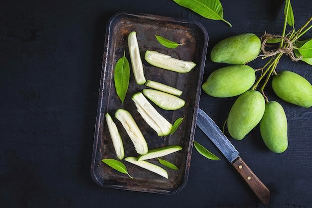 Mangue verte fraîche tranchée sur un plateau Photo Premium