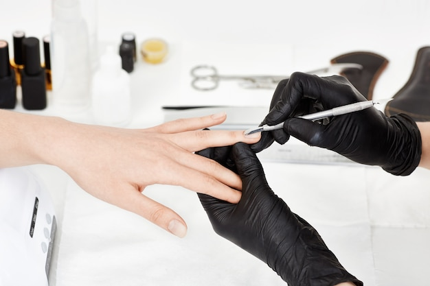 Manicrurist Dans Des Gants Poussant La Cuticule Sur L'annulaire De La Femme. Photo gratuit