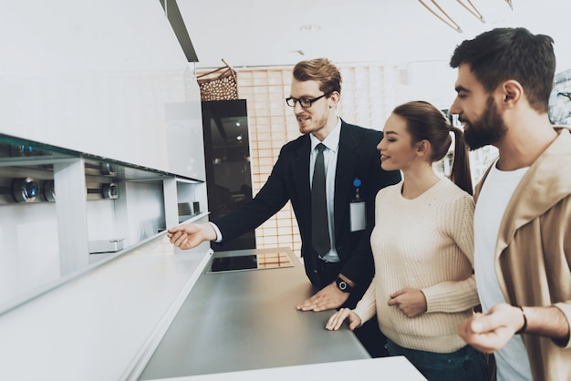 Manin costum montre une nouvelle cuisine pour quelques clients. Photo Premium