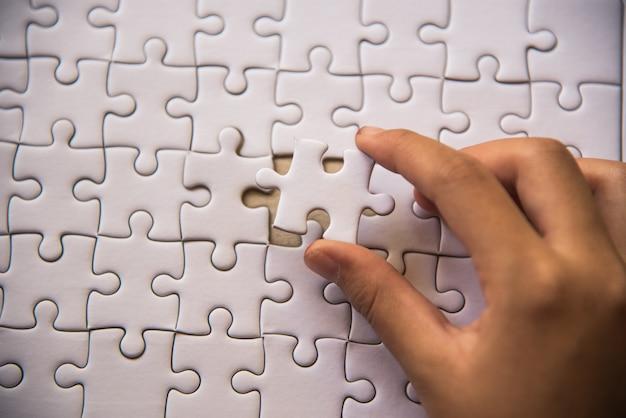 Manipulez un morceau de casse-tête blanc sur le point de tomber pour obtenir une feuille de travail complète. Photo Premium