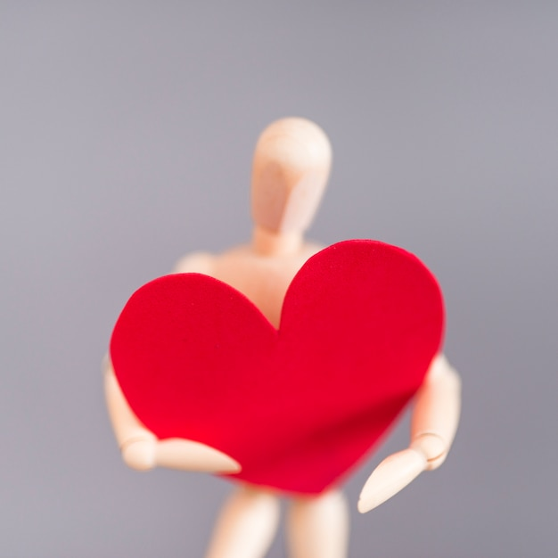 Mannequin en bois tenant grand coeur rouge Photo gratuit