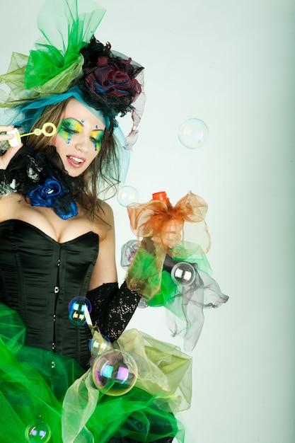 Mannequin avec maquillage créatif soufflant des bulles de savon. Photo Premium