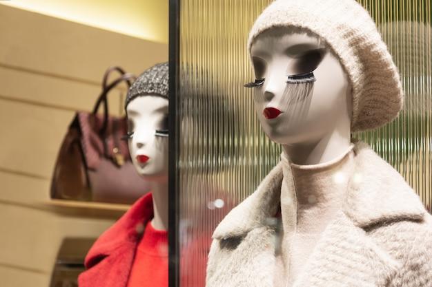 Les mannequins du magasin aux lèvres brillantes et aux longs cils montrent les vêtements d'hiver. Photo Premium