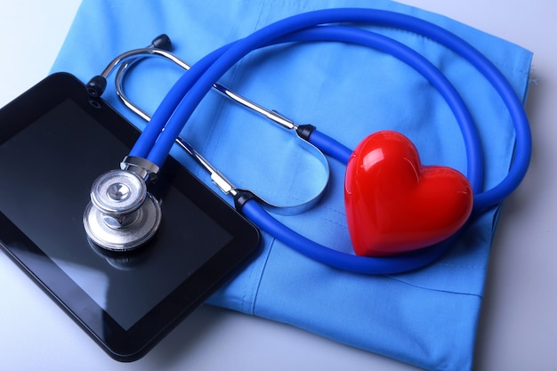 Manteau de docteur avec stéthoscope médical et coeur rouge sur le bureau Photo Premium