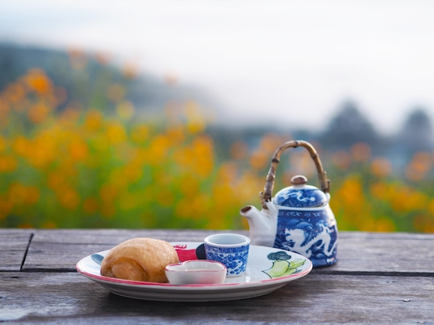 Mantou Frit Avec Du Lait Concentré Et Du Thé Chinois Sur Une Table En Bois à L'extérieur Photo Premium