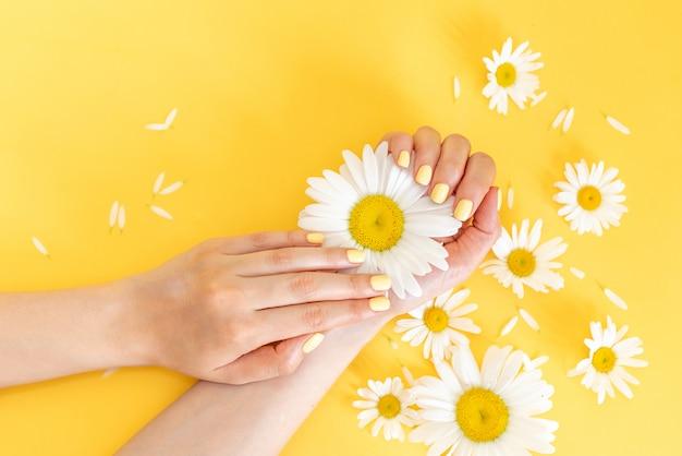 Manucure femme tendance élégante. mains de la belle jeune femme sur fond jaune. Photo Premium