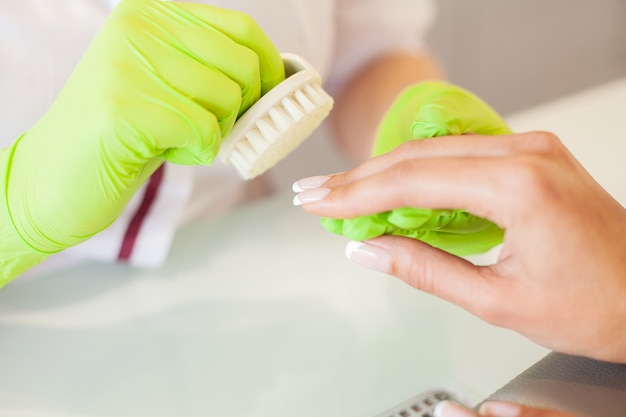 Manucure. habile manucure tenant son dossier dans ses mains alors qu'elle travaillait dans son salon de beauté Photo Premium