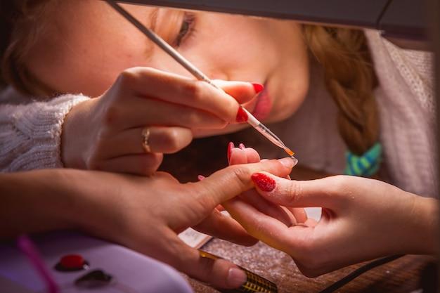 Manucure. master make extension de l'ongle: dessin du gel blanc sur le bord libre d'un ongle Photo Premium
