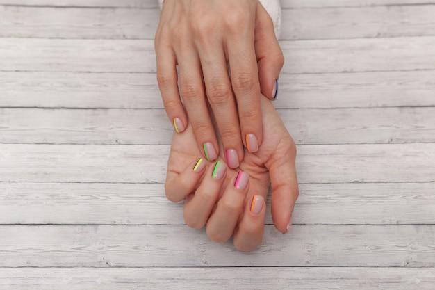 Manucure moderne multicolore, design des ongles. ambiance estivale, sur fond de bois. vue de dessus Photo Premium