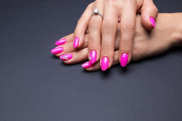 Manucure stylisée rose sur fond noir Photo Premium