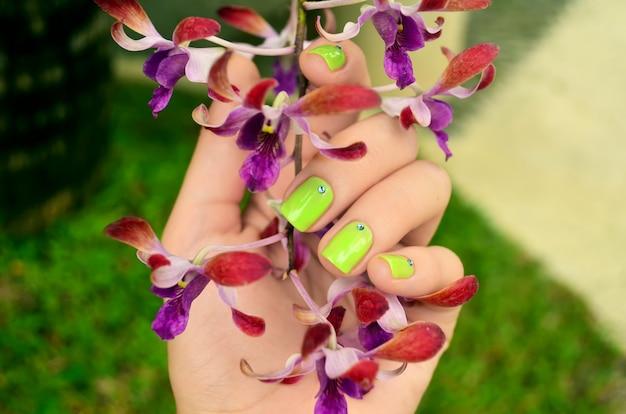 Manucure Verte Avec De Belles Fleurs D'orchidées Photo Premium