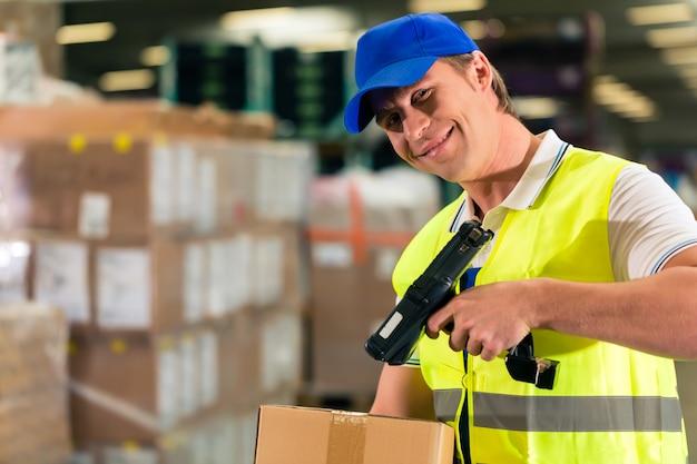 Manutentionnaire avec gilet de protection et scanner, scanne le code à barres du colis, il se tient devant l'entrepôt d'une entreprise de transport Photo Premium