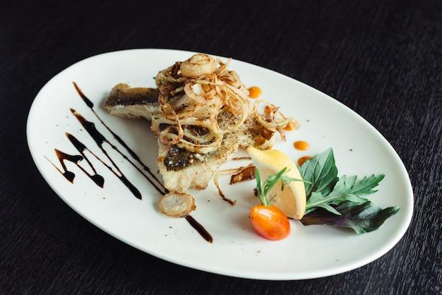 Maquereau grillé à l'oignon sur une plaque blanche sur une table en bois Photo Premium