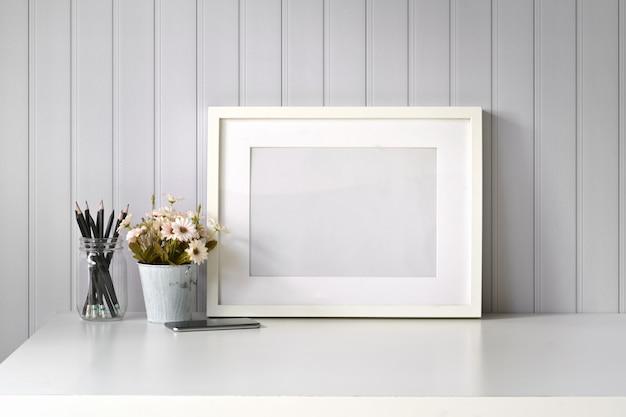 Maquette affiche une image vierge sur un bureau blanc Photo Premium