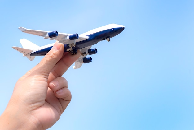 Maquette d'avion à la main sur ciel ensoleillé. concepts de voyage, de transport Photo Premium