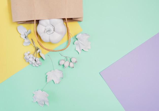 Maquette blanche avec citrouille, baies, feuilles et paquet sur un fond d'automne multicolore pastel Photo Premium