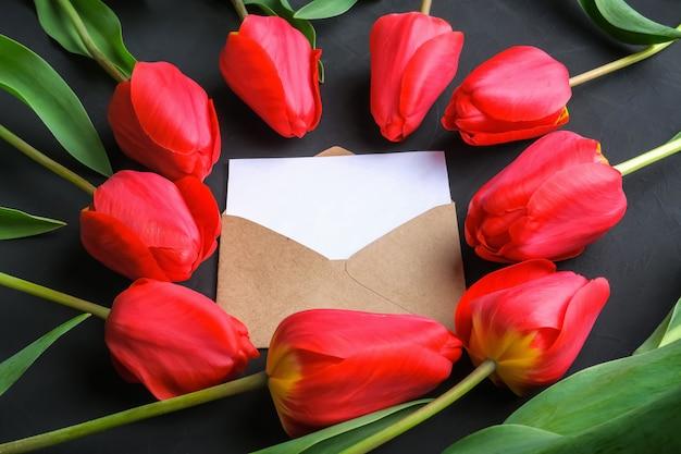 Maquette de bouquet de tulipes rouges fraîches et carte de voeux dans une enveloppe kraft Photo Premium