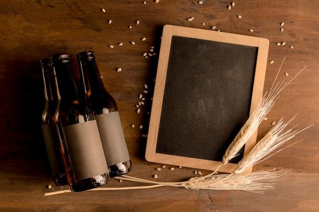 Maquette de bouteilles de bière brune avec tableau noir sur une table en bois Photo gratuit