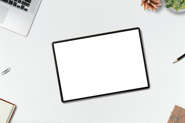 Maquette de bureau avec tablette à écran blanc, ordinateur portable et fournitures Photo Premium