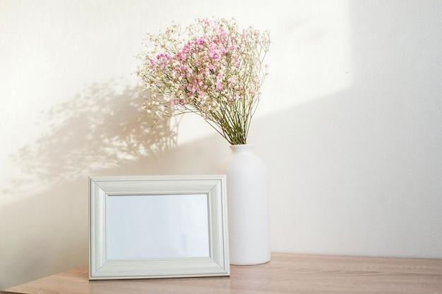 Maquette De Cadre Blanc Horizontal Sur Banc En Bois Vintage, Table. Vase Moderne En Céramique Blanche Gypsophile. Fond De Mur Blanc. Photo Premium