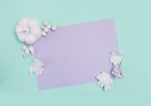 Maquette de cadre avec citrouille, baies et feuilles sur carte turquoise et violette Photo Premium