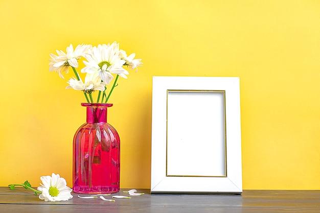 Maquette de cadre avec des fleurs d'aster tendre dans un vase élégant de couleur rose. poster maquette cadre blanc. em Photo Premium