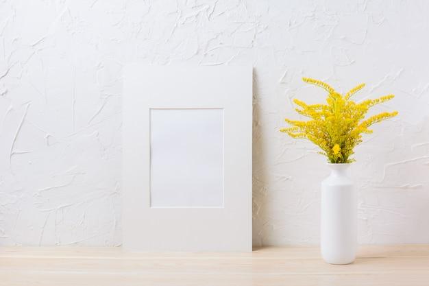 Maquette De Cadre Mat Blanc Avec De L'herbe à Fleurs Jaunes Ornementales Dans Un Vase Photo Premium