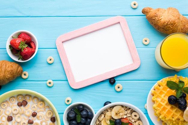 Maquette de cadre plat poser sur la table de petit déjeuner Photo gratuit